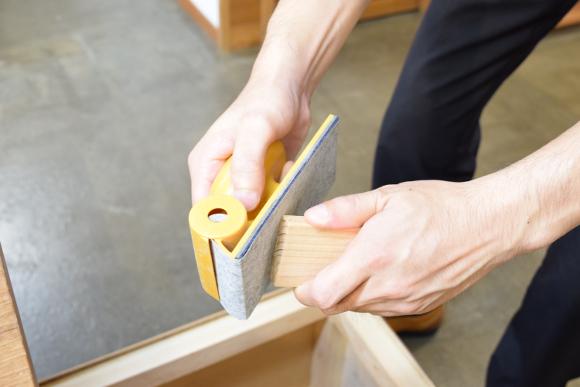 カドやざらつきを紙やすりで削る様子。
